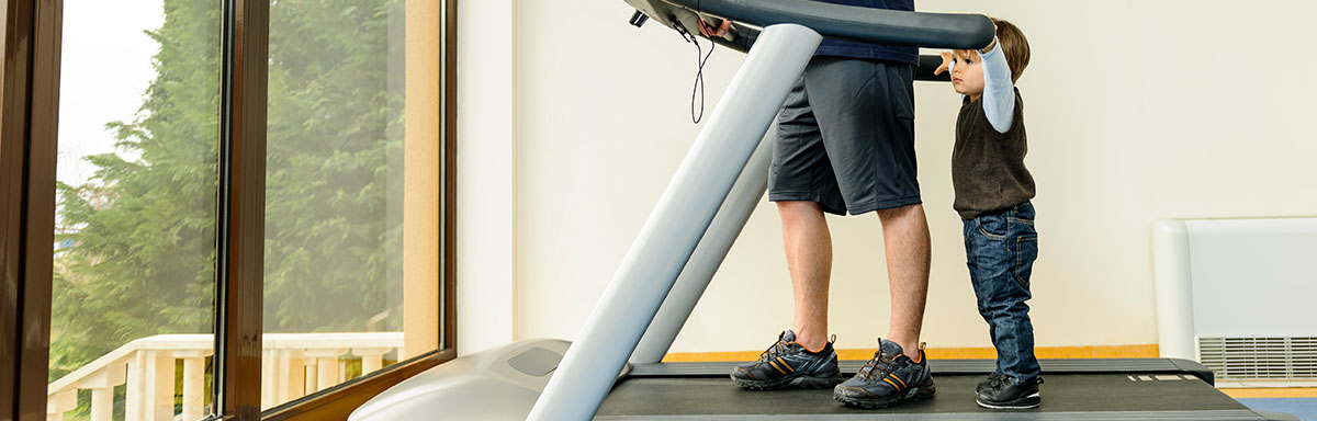 dad and son on at home exercise equipment